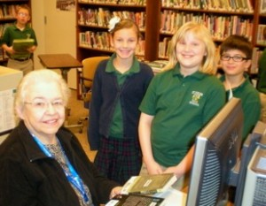 St. Helen School librarian Sr. Bernadette takes a break from checking out books for fourth-graders Rosie Murray, Sarah Robinson and Ricky Hoenigman. (Submitted)