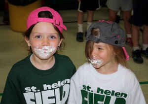 Submitted St. Helen School kindergartners Noelle Rudersdorf and MacKenzie Hart are all smiles after retrieving a cookie covered in whipped cream without using their hands during field day.