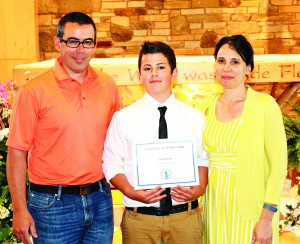 St. Helen School eighth-grader J.K. Gray is the winner of the Benedictine Merit Scholarship Award. With J.K. are his parents, Kevin and Ruthann.